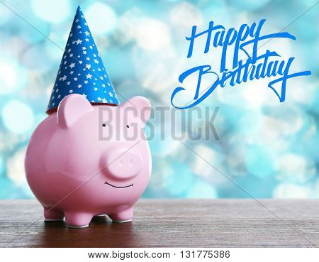 Piggy bank with birthday hat on blurred festive background