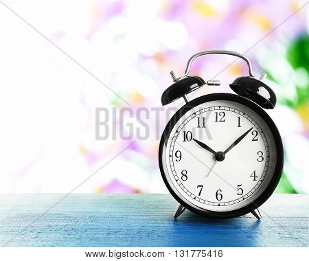 Summer time concept. Alarm clock on wooden table on  field background
