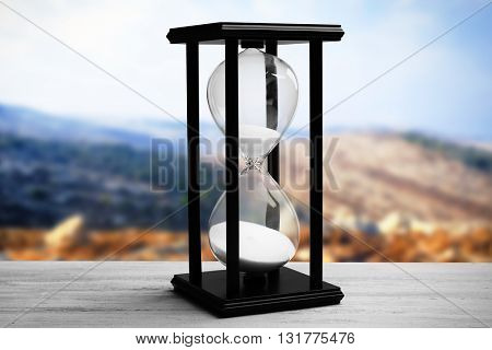Black hourglass on blurred natural background