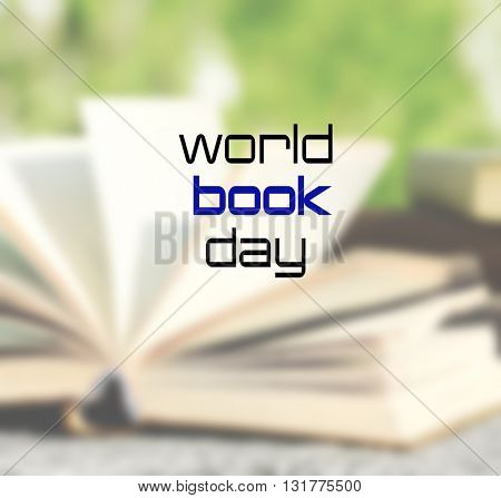 Stack of books in park on blurred background. World Book Day poster