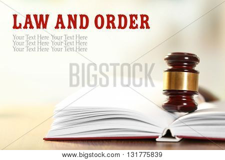 Wooden judges gavel lying on law book, close up. Law and order concept