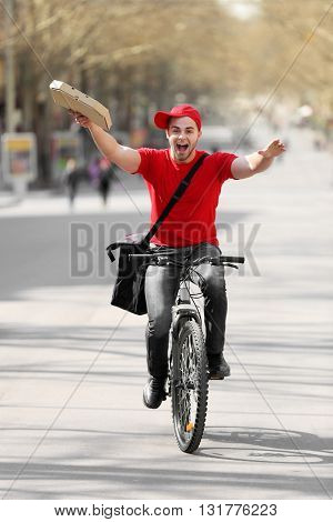 Young man with bike delivering pizza