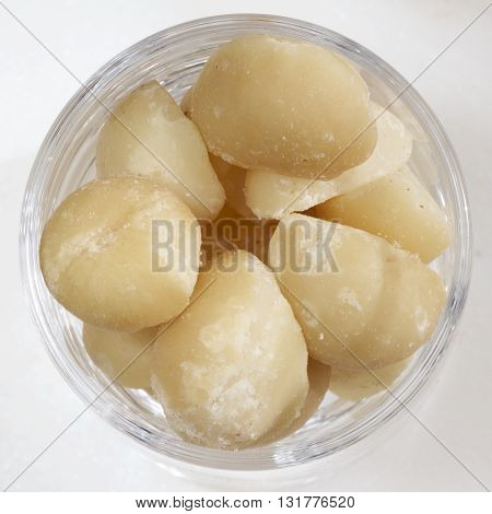 Some macadamia nuts in a small glass.