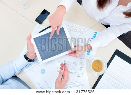 Businessman discussing with financial analyst business development strategy project and using modern digital tablet with chart on a screen. Top view photoshoot.