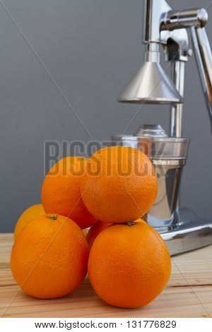 Oranges and chrome citrus juicer over a wood table on natural environment.