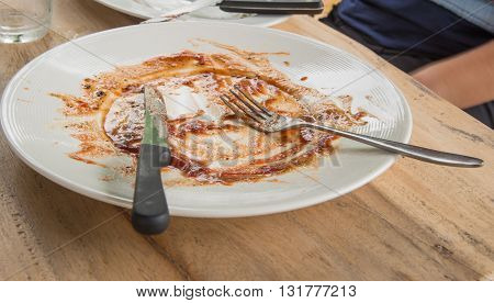 Dirt platePlate Spaghetti dirty cutlery placed on wooden table.