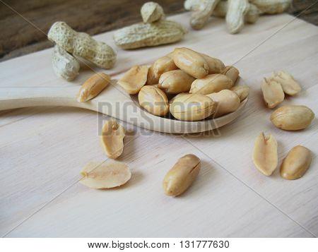 Peeled salted peanuts on wooden spoon .