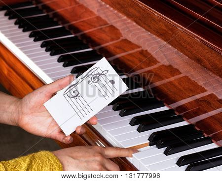 Close up of female hands holding music key card to show exact location on piano keyboard. Select focus on music key card.