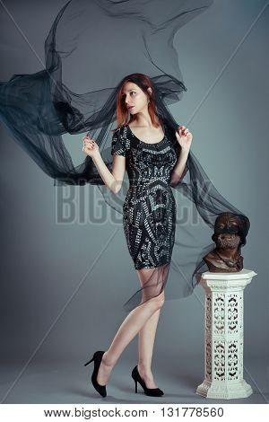 Red hair woman posing in the studio with big black muslin fabric