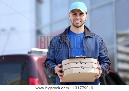 Young man holding pizza outside
