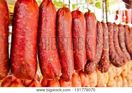 Home made meat salami sausage at street market hanging in line under sunlight to make good tasty
