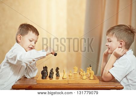 two boys dressed in white are playing chess on the table