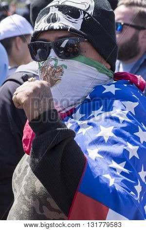 SAN DIEGO USA - MAY 27 2016: A man disguised in a Mexican bandana skull hoodie dark shades and an American flag cape clenches his fist in a gesture signifying Chicano power at anti-Trump protest in San Diego