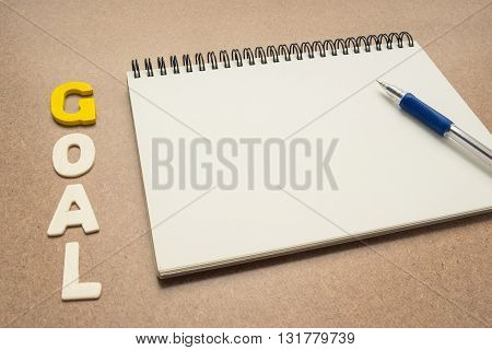 GOAL wording with open spiral notebook and pen on brown background - concept of setting goal business
