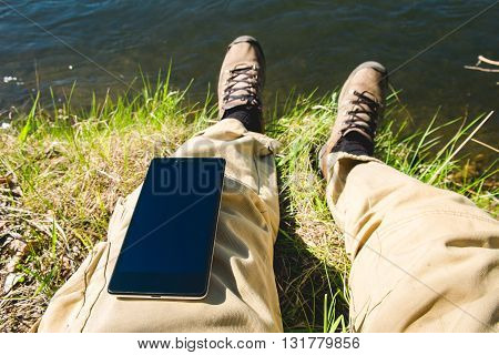 Man uses smartphone mobile sitting on the river shore