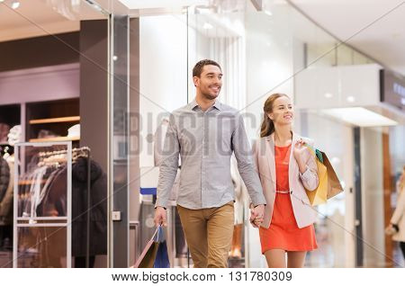 sale, consumerism and people concept - happy young couple with shopping bags walking in mall