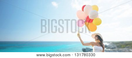 travel, tourism, summer, holidays and people concept - smiling young woman wearing sunglasses with balloons over exotic tropical beach and sea background