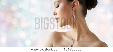 beauty, jewelry, wedding accessories, people and luxury concept - beautiful asian woman or bride with earring and pendant over blue holidays lights background