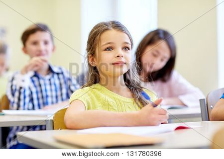education, elementary school, learning, children and people concept - student girl with group of classmates on lesson in classroom