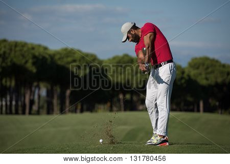 golf player hitting shot with driver on course at beautiful sunny day