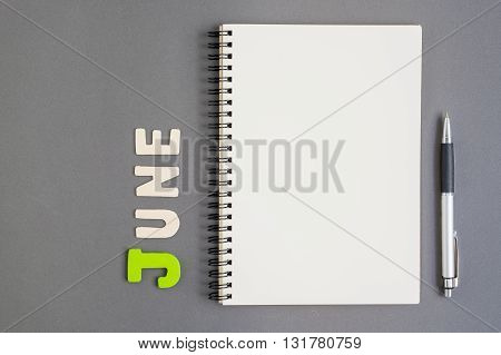 Spiral open notebook with pen and June month wording on grey background