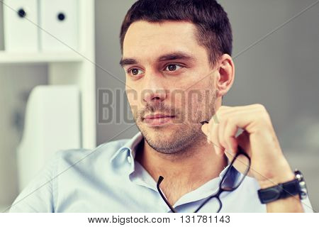 business, people and work concept - portrait of businessman with eyeglasses at office