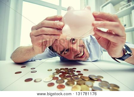 business, people, finances and money saving concept - happy businessman shaking piggy bank and getting coins at office