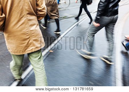 picture of people crossing a city street with tram lines shown in motion blur
