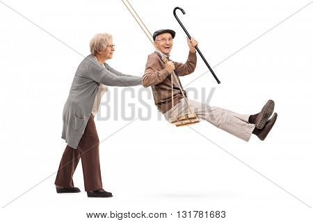 Elderly woman pushing a man on a wooden swing isolated on white background