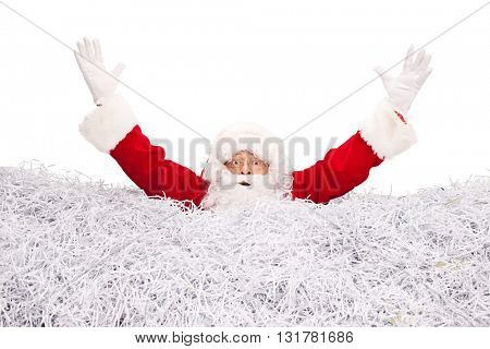 Studio shot of Santa Claus drowning in a pile of shredded paper isolated on white background