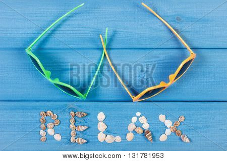 Inscription relax made of seashells and sunglasses on blue boards summer and vacation time