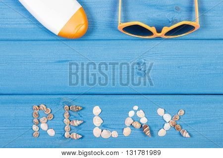 Inscription relax made of seashells sunglasses and sun lotion on blue boards summer and vacation time copy space for text