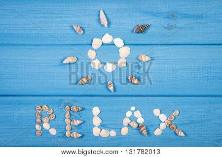 Inscription relax and shape of sun made of seashells on blue boards summer and vacation time