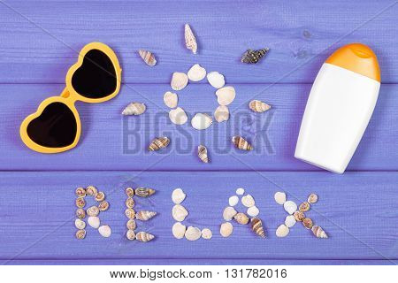 Inscription relax and shape of sun made of seashells sunglasses and sun lotion on purple boards summer and vacation time