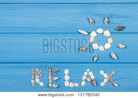 Inscription relax and shape of sun made of seashells on blue boards summer and vacation time copy space for text