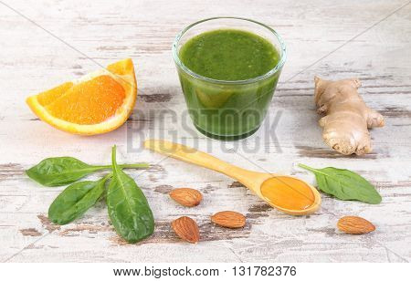Ingredients and spices for fresh green nutritious cocktail from spinach on old rustic wooden background healthy nutrition