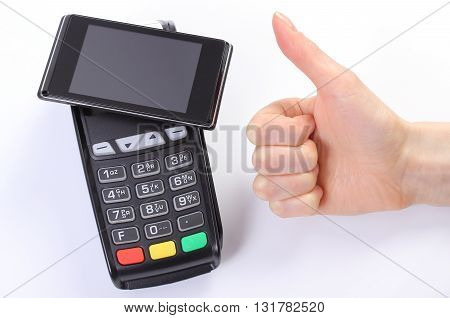 Banking and finance concept Hand of woman showing thumbs up and payment terminal with mobile phone with NFC technology credit card reader