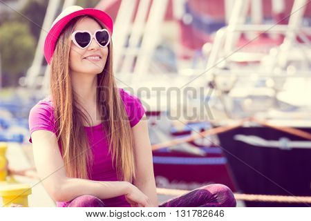 Happy woman tourist with straw hat and sunglasses in shape of heart in port with yacht in background travel summer and vacation time