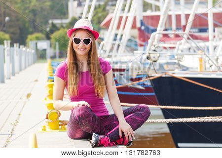 Happy smiling woman tourist with straw hat and sunglasses in shape of heart on pier in port with yacht travel summer and vacation time