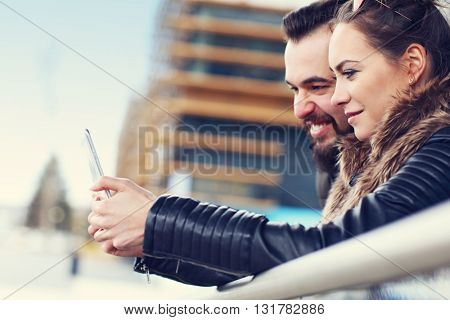 Picture of young couple hanging out in city and texting