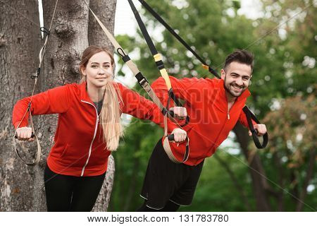 Happy smiling sport man and woman training in park with suspension trainer sling. Beautiful couple of husband and wife doing sport exercises.
