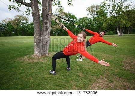 Fitness woman exercising with suspension trainer and personal sport trainer in city park under summer trees. Fitness and sport concepts.