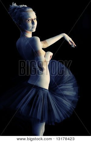Artistic woman painted with  white and bronze colors, over black background. Body painting project.