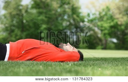 Handsome sport man training in park. Athlete in red jacket lying on green grass and doing trunk curls. Fitness and lifestyle concepts.