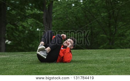 Sport man training in green park. Handsome man in red jacket lying on green grass and doing different exercises for abs.