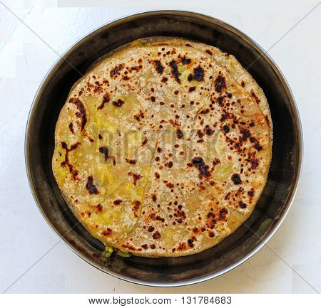 Indian aloo or potato parathas or bread platters kept inside a container on plain background