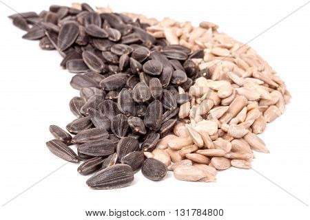 sunflower seeds peeled and unpeeled isolated on white background.