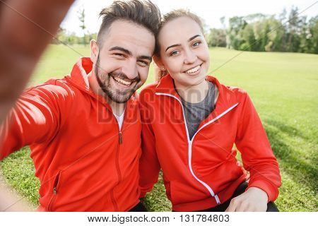 Closeup portrait of sport man and woman making selfies in green park or forest while sitting on green grass and resting after jogging.