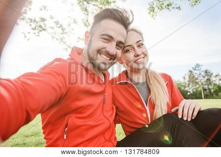 Low view of sport man and woman making selfies in green park. Happy couple posing for camera and hugging. Smiling couple resting and relaxing.