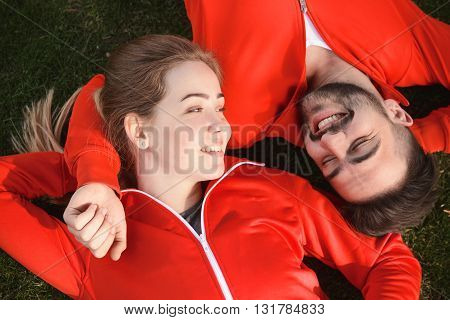 Happy sport man and woman resting and relaxing on green grass in park. Beautiful fitness couple smiling to each other.